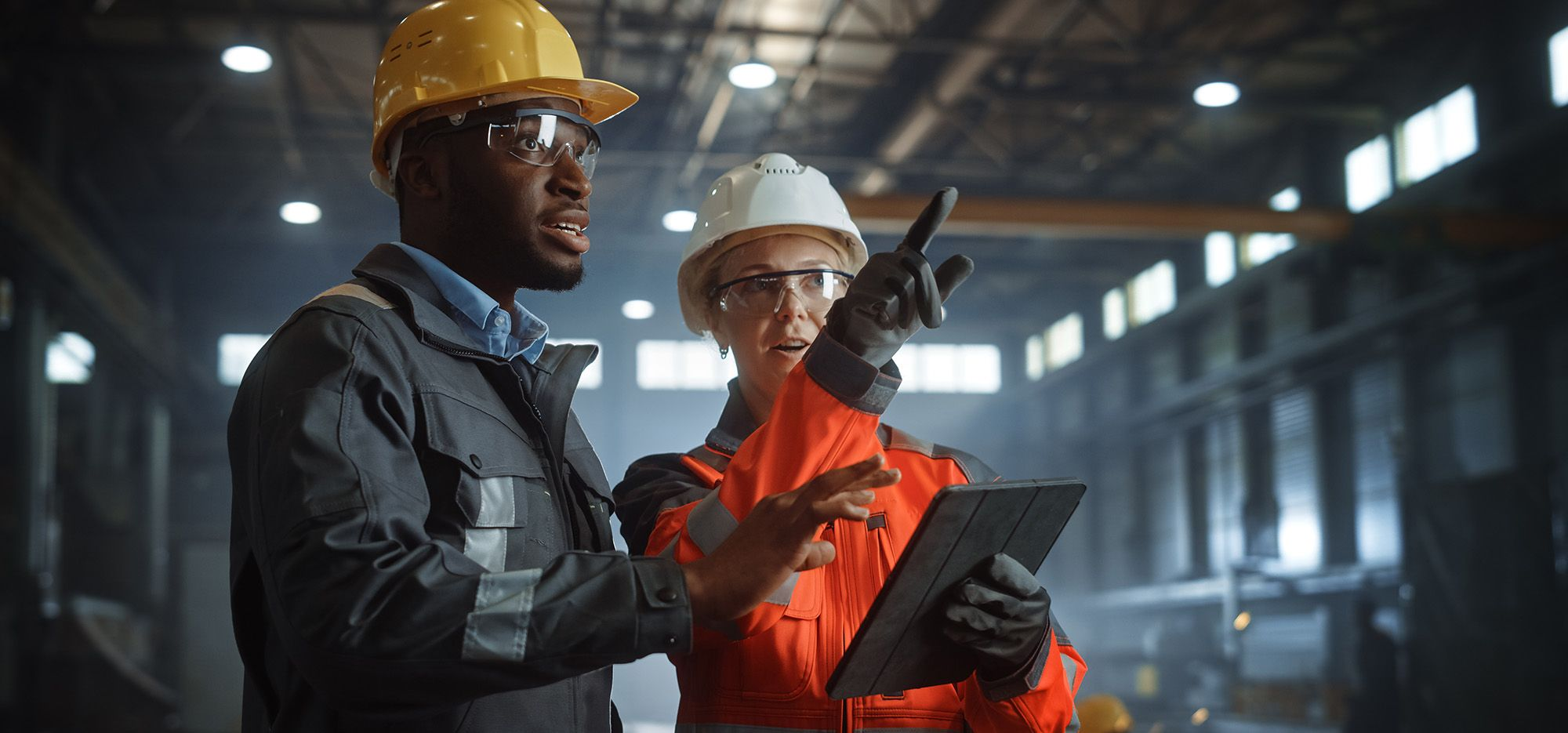 woman-and-man-inspecting-industrial-plant